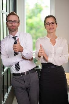 Homem de negócio e mulher de sorriso que mostram os polegares acima.
