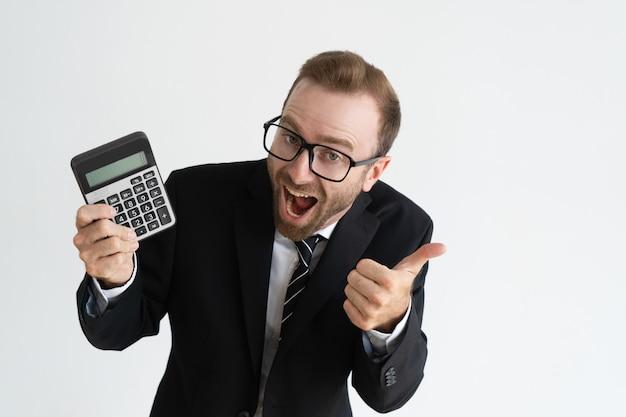 Homem de negócio entusiasmado que mostra o indicador e o polegar da calculadora. conceito de cálculo.