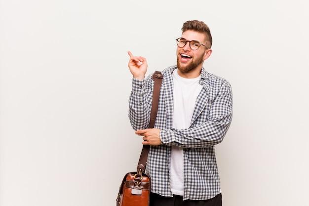 Homem de negócio moderno novo que sorri alegremente apontando com dedo indicador afastado.