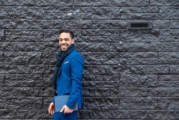 Homem de negócio no terno azul que leva uma tabuleta fora.
