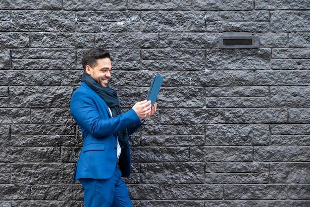 Homem de negócio no terno azul que toma a imagem com tabuleta.