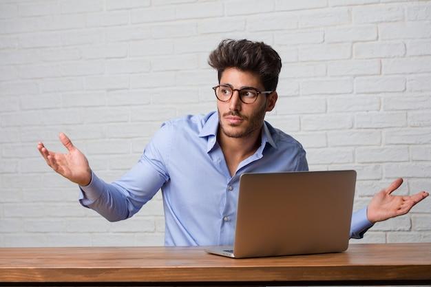 Homem de negócio novo que senta-se e que trabalha em um portátil que duvida e que encolhe ombros, conceito da indecisão e insegurança, incerto sobre algo