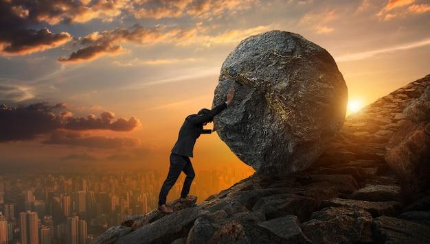 Homem de negócio que empurra a grande pedra até o monte, tarefas pesadas do negócio e conceito dos problemas.