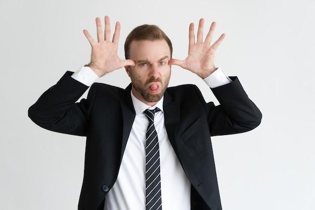 Homem de negócio que guarda as mãos perto da cara, fazendo caretas e olhando a câmera.