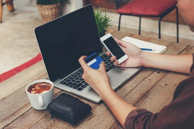 Homem de negócio que guarda o cartão de crédito do telefone e do pagamento com o portátil na tabela de madeira.