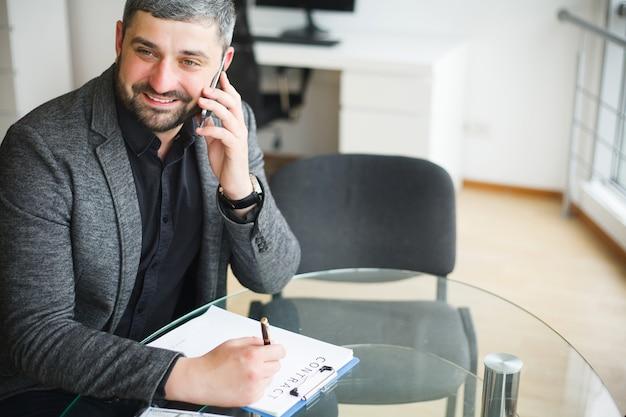 Homem de negócio que senta-se na mesa e no contrato de assinatura.