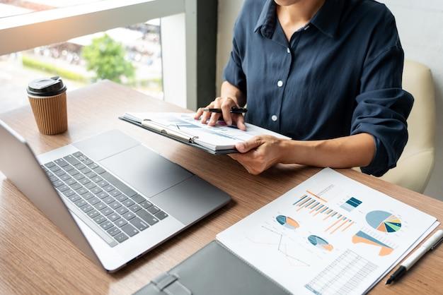 Homem de negócio que trabalha com dados do gráfico no portátil e nos originais em sua mesa no escritório.