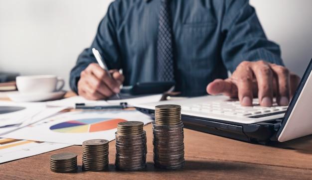 Homem de negócio que trabalha e que escreve no caderno com a pilha de moedas para o conceito financeiro e de contabilidade.