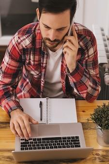 Homem de negócio que trabalha no laptop em casa e que chama o telefone.