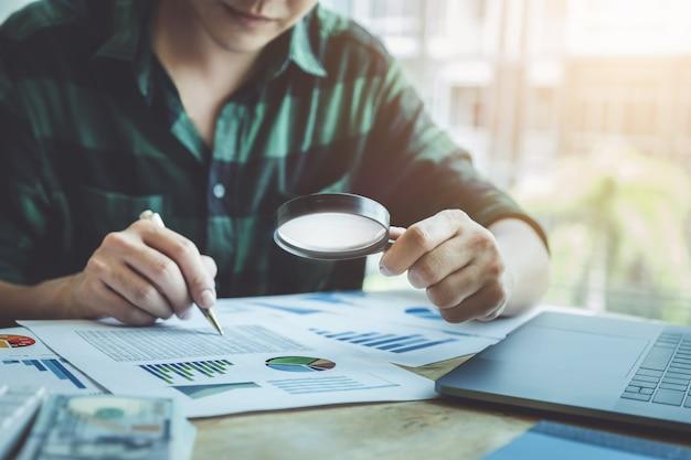 Homem de negócio que usa a ampliação para rever o anuário do balanço patrimonial com utilização do laptop ao orçamento calculador. auditar e verificar a integridade antes do conceito de investimento.