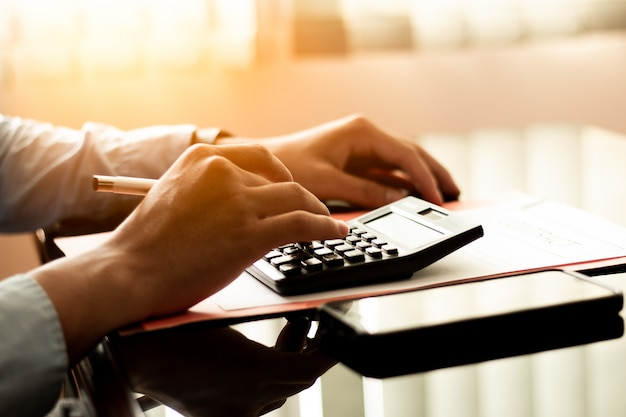 Homem de negócio que usa a calculadora com o papel do portátil, do orçamento e do empréstimo no escritório.