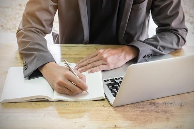 Homem de negócio que usa a pena e o portátil que escreve então no caderno no local de trabalho.