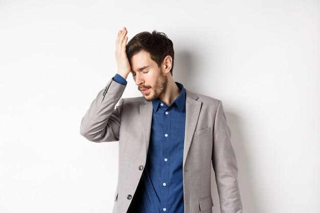 Homem de negócios aborrecido de terno, cara palmas com os olhos fechados, incomodado por alguém estúpido