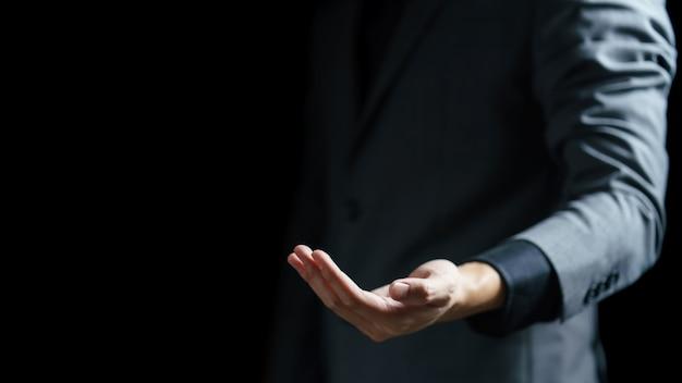 Homem de negócios abre mão vazia em fundo preto.