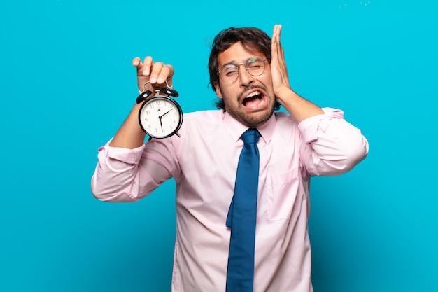 Homem de negócios adulto bonito indiano com despertador
