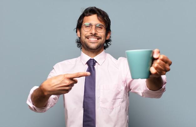 Homem de negócios adulto bonito indiano com uma xícara de café