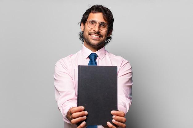 Homem de negócios adulto bonito indiano segurando um caderno