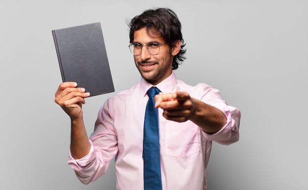 Homem de negócios adulto bonito indiano segurando um livro