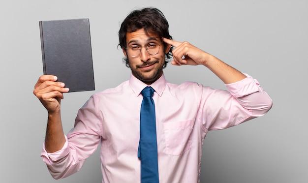 Homem de negócios adulto bonito segurando um livro
