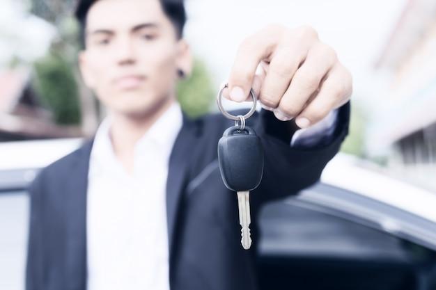 Homem de negócios adulto masculino em um terno e segurando uma chave do carro em sua mão. carros brancos ao fundo