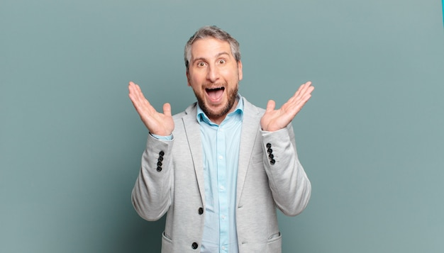 Homem de negócios adulto parecendo feliz e animado, chocado com uma surpresa inesperada com as duas mãos abertas ao lado do rosto