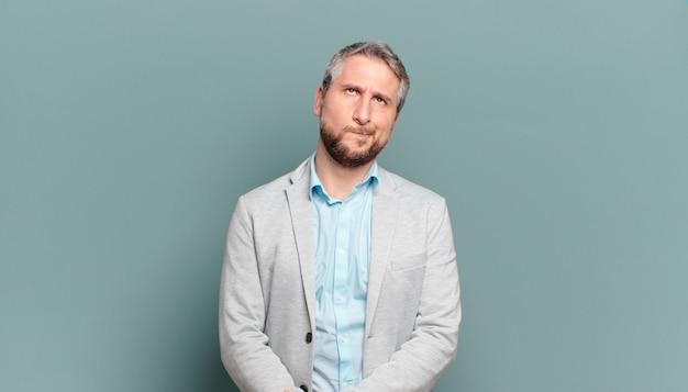 Homem de negócios adulto parecendo perplexo e confuso, pensando ou tentando resolver um problema ou pensamento