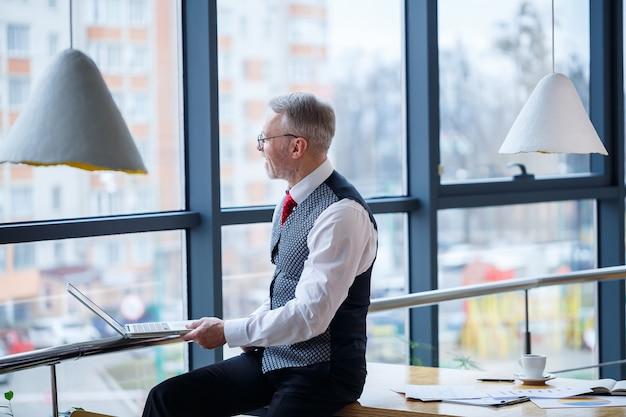Homem de negócios adulto, professor, mentor trabalhando em um novo projeto. senta-se junto a uma grande janela sobre a mesa. ele olha para a tela do laptop.