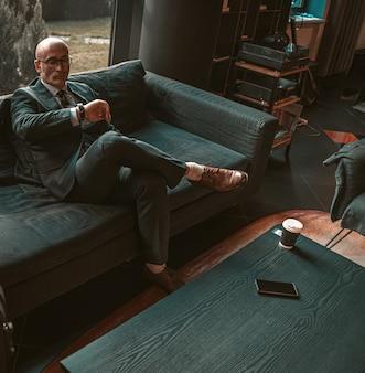 Homem de negócios adulto respeitável e careca olhando para os relógios na mão esperando por uma reunião de negócios