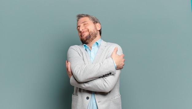 Homem de negócios adulto se sentindo apaixonado, sorrindo, acariciando e abraçando a si mesmo, permanecendo solteiro, sendo egoísta e egocêntrico