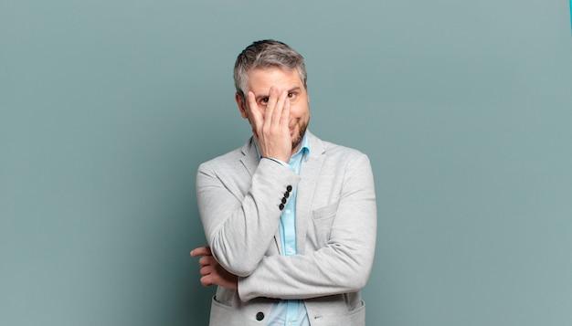 Homem de negócios adulto se sentindo entediado, frustrado e com sono após uma tarefa cansativa, enfadonha e tediosa, segurando o rosto com a mão