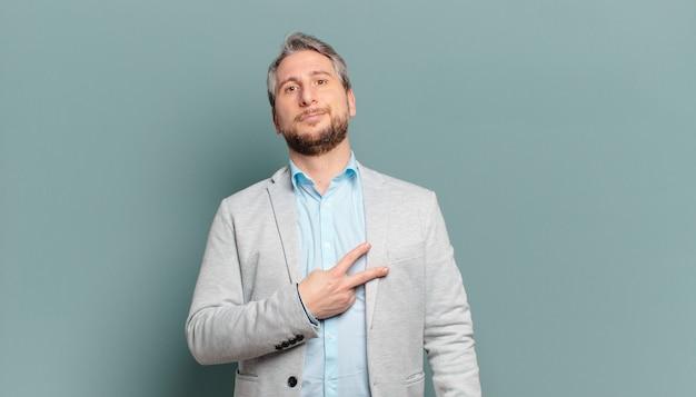 Homem de negócios adulto se sentindo feliz, positivo e bem-sucedido, com a mão em forma de v sobre o peito, mostrando vitória ou paz
