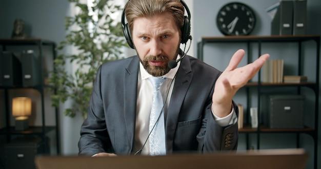 Homem de negócios adulto sentado em frente ao computador com fone de ouvido usando-o para falar com o cliente ou parceiro e gesticulando