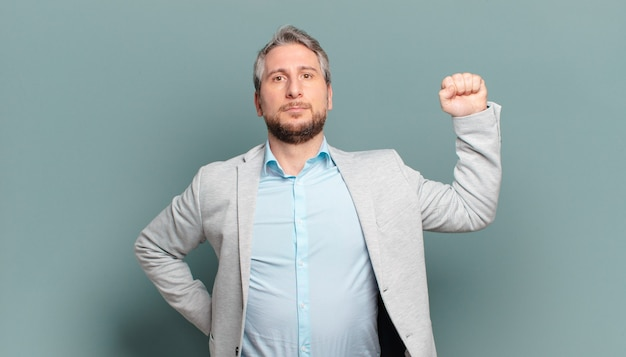 Homem de negócios adulto sentindo-se sério, forte e rebelde, levantando o punho, protestando ou lutando pela revolução
