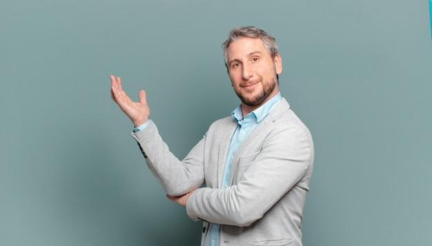 Homem de negócios adulto sorrindo com orgulho e confiança, sentindo-se feliz e satisfeito e mostrando um conceito no espaço da cópia