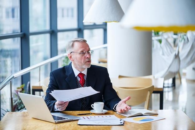 Homem de negócios adulto trabalhando em um novo projeto e olhando os gráficos de crescimento das ações. senta-se em uma grande janela na mesa. olha para a tela do laptop e bebe café.