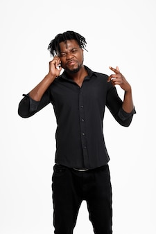 Homem de negócios africano bem sucedido novo que fala no telefone no branco.