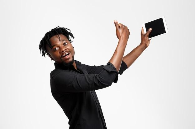 Homem de negócios africano bem sucedido novo que faz o selfie no branco.