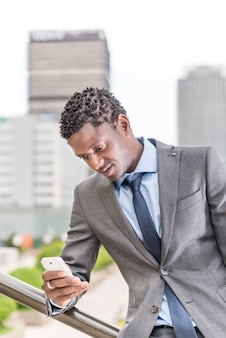 Homem de negócios africano com smartphone sobre prédio de escritórios - conceito de tecnologia e pessoas
