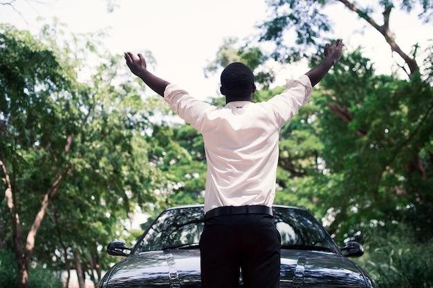 Homem de negócios africano da liberdade no terno que está o carro próximo com fundo natural verde.