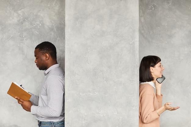 Homem de negócios africano lendo seu bloco de notas com uma mulher de negócios falando no celular, eles parados atrás da parede branca