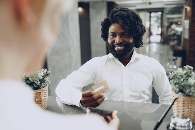 Homem de negócios africano pagando estadia no hotel com cartão de crédito