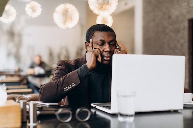 Homem de negócios africano que pensa e cansado ao trabalhar no portátil em um restaurante.