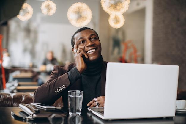 Homem de negócios africano que pensa e que sorri ao trabalhar no portátil em um restaurante.