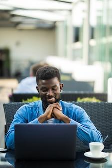 Homem de negócios africano sentado à mesa em um café, trabalhando com um laptop e papéis e bebendo café
