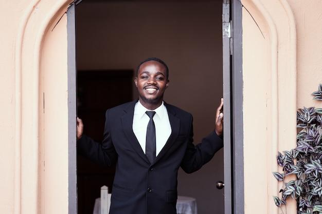 Homem de negócios africano sorrir e abrir a porta