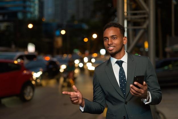 Homem de negócios africano usando um aplicativo para celular esperando um táxi com a mão levantada à noite