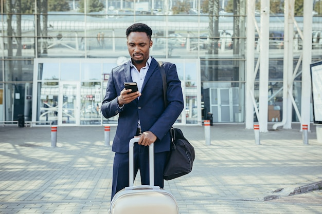 Homem de negócios africano viajando perto do aeroporto com uma mala chamando um táxi usando um aplicativo móvel