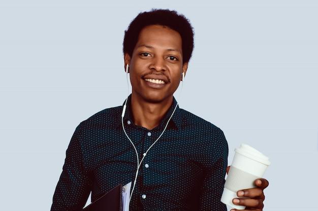 Homem de negócios afro-americano com dobradores e café.