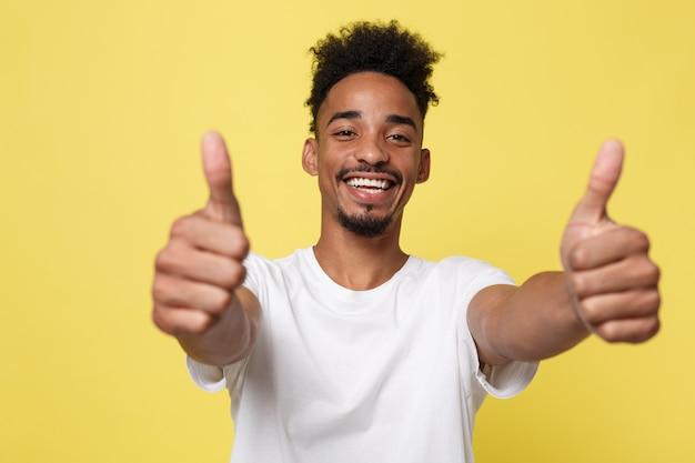 Homem de negócios afro-americano feliz isolado no fundo amarelo.