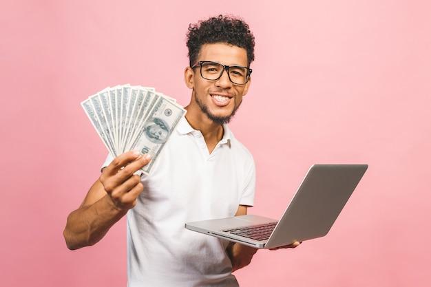 Homem de negócios afro-americano ganhando dinheiro com a internet, segurando dinheiro na mão e laptop em outra